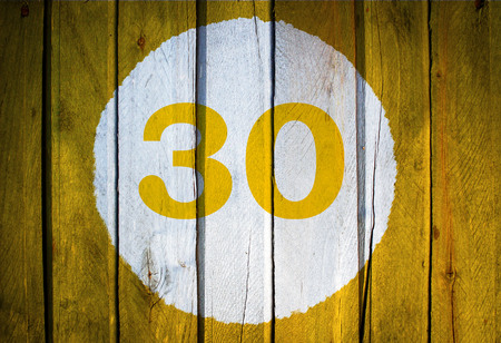 House number or calendar date in white circle on yellow toned wooden door background. Number thirty 30