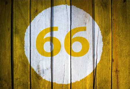 House number or calendar date in white circle on yellow toned wooden door background. Number sixty six, 66