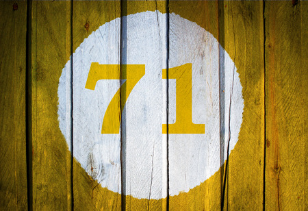 House number or calendar date in white circle on yellow toned wooden door background. Number seventy one 71