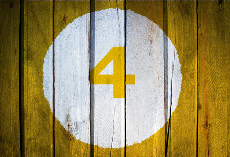 House number or calendar date in white circle on yellow toned wooden door background. Number four 4 Stock Photo