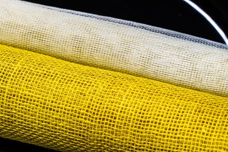 Yellow and white jute, floristic net rolled up. on a black background