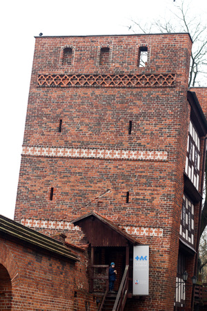 Medieval leaning defence tower of Torun over white sky Editorial