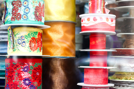 Various choice of different colorful decorative ribbons at traditional notions store. Display macro close up with window reflections. Poland, Torun