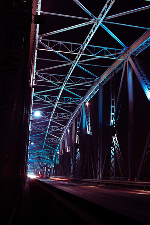 Detail of a bridge with road for cars at night. Many lights over dark sky.
