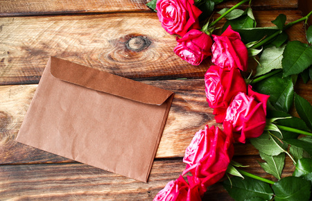 Bouquet of red roses on wooden background. Valentines Day background with mysterious brown envelope. Love letter