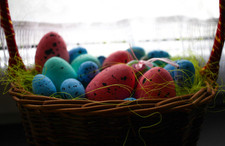 Small painted Easter eggs in a basket. Pink blue green colors. Decoration