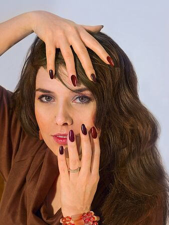 bangles hand: Portrait of pretty young attractive woman in a brown dress. Demonstrates manicure. Stock Photo