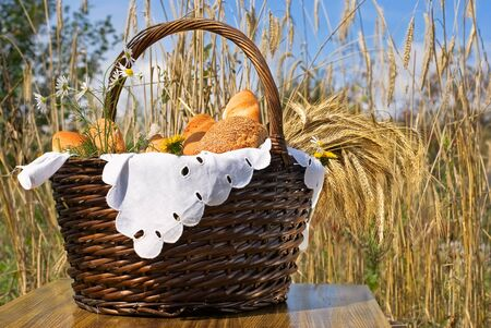 Basket with bakery products on the background of wheat ears.
