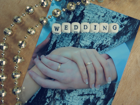 wedding photography: Wedding photography, feather and word of beads on a wooden surface Stock Photo