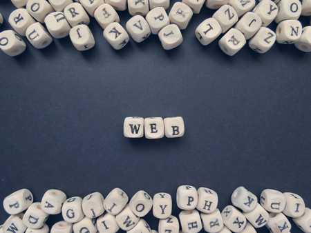 jumbled: Word Web of small white cubes next to a bunch of other letters on the surface of the composition on a dark background Stock Photo