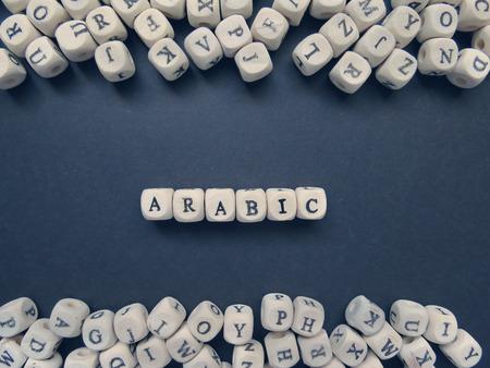 arabische letters: Word het Arabisch van kleine witte blokjes naast een heleboel andere letters op het oppervlak van de samenstelling op een donkere achtergrond