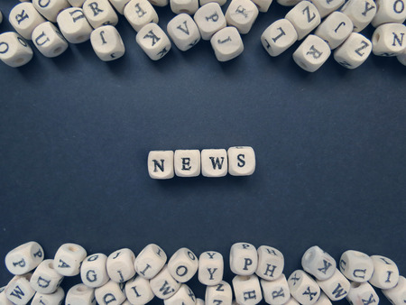 jumbled: Word News of small white cubes next to a bunch of other letters on the surface of the composition on a dark background Stock Photo