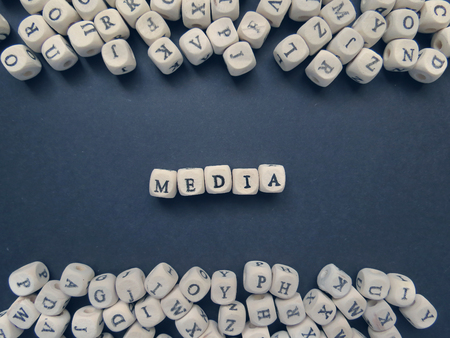 jumbled: Word Media of small white cubes next to a bunch of other letters on the surface of the composition on a dark background Stock Photo