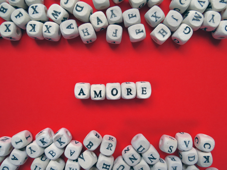 amore: Word Amore meaning Love in Italian language as a composition of wooden block letters against the red background