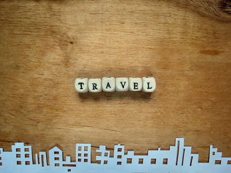 aeronautics: Word Travel from the small cubes and the city cut out of paper on a wooden surface