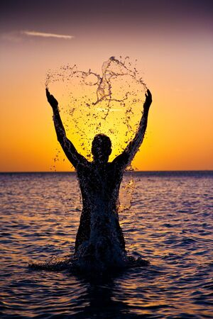 silhoutted: Man splashes in the water, silhoutted at sunset. Stock Photo