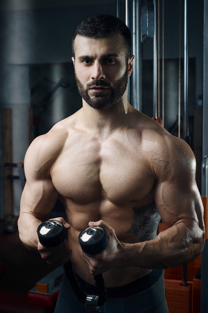 physique: Mens physique athlete doing standing rope curls in the gym
