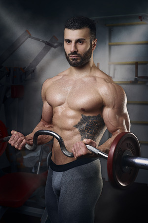 physique: Mens physique athlete doing standing EZ-Bar curls in the gym