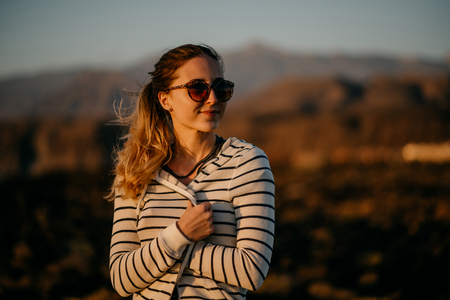 Charming girl stands on the rock near the ocean in the evening on the sunset in the sunglasses. Tenerife Stock Photo