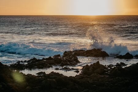 Beautiful peachy sunset with huge ocean waves in the Tenerife