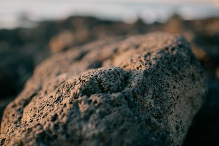 Volcanic stone on the rocky shore of the ocean on the sunset. Tenerife Stock Photo