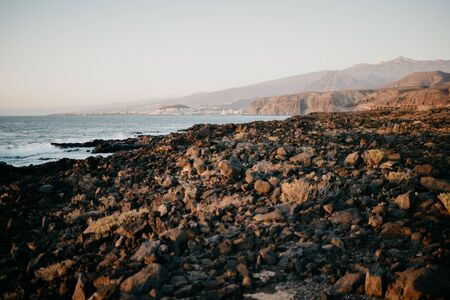Rocky shore of the ocean on the sunset. Tenerife Stock Photo