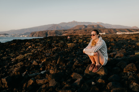 Charming girl in the sunglasses sits on the stone and waits for the sunset in the evening. Tenerife Stock Photo