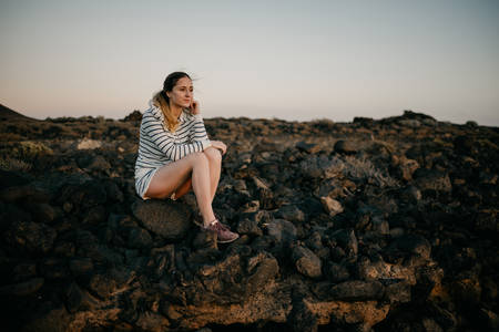 Girl sitting on the rock in the evening. Tenerife