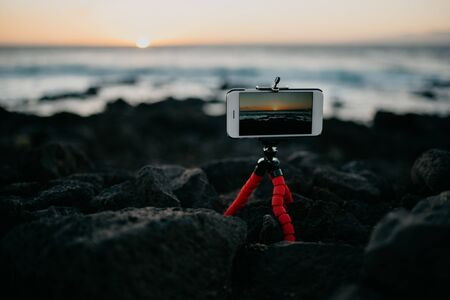 Mobile phone on the tripod shooting the sunset on the rocky shore of the ocean. Tenerife