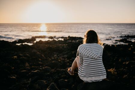 Girl sitting on the rock near the ocean in the evening on the sunset in the sunglasses. Tenerife Stock Photo