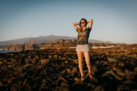 Girl enjoys on the rock near the ocean in the evening on the sunset in the sunglasses. Tenerife Stock Photo
