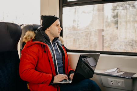 Man at the red jacket with the laptop going by the train and watching at the window Stock Photo