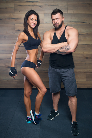 Muscular man with tattoos and beard and beauty girl posing in a black tank top and black shorts in the gym