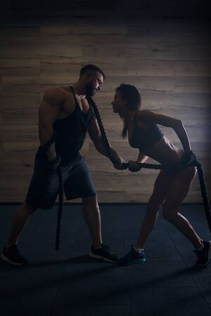 Muscular man with tattoos and beard and beauty girl pulling a rope in a black tank top and black shorts in the gym. Silhouette