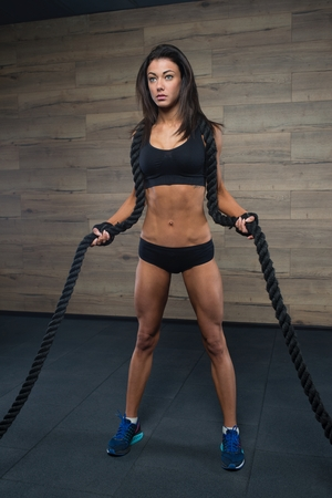 Fit girl with black hair in the black shorts, shorts and gloves stands with rope in the gym, wooden wall at background Stock Photo