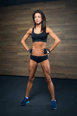 Shredded fit girl with black hair wearing black short top, shorts and gloves Stock Photo