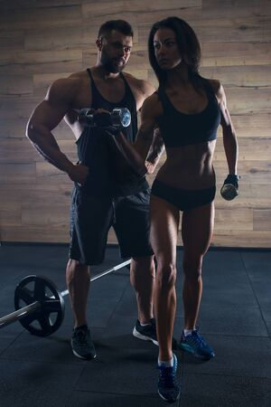 Muscular man with tattoos and beard and beauty girl posing in a black tank top and blue shorts in the gym. Silhouette