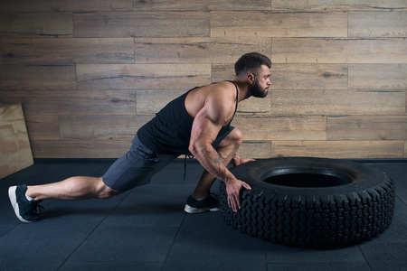 Muscular man with beard pushing a tire in a black tank top and gray shorts in the gym