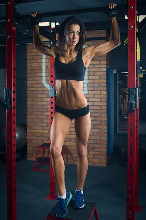 Fit girl with black hair wearing black short top, shorts and gloves standing with horizontal bar on box in gym, brick wall at background