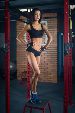 Fit girl with black hair wearing black short top, shorts and gloves standing on box in gym, brick wall at background
