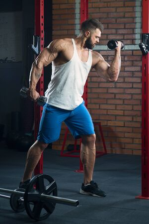 Muscular man with tattoos and beard doing biceps with dumbbell in a white tank top and blue shorts in the gym