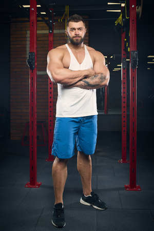 Muscular man with tattoos and beard posing in a white tank top and blue shorts in the gym