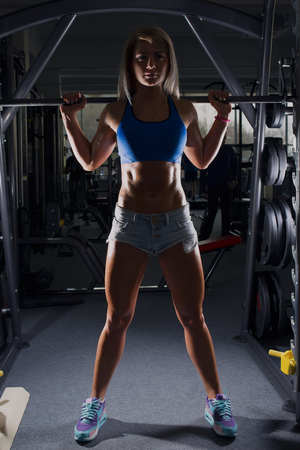 Fit girl standing on the smith in the gym in a denim shorts and blue top. Silhuette