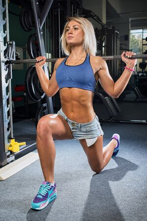 Fit girl doing lunges with the smith machine in the gym in a denim shorts and blue top Stock Photo
