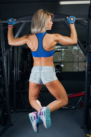 Fit girl catching up on the bar in a denim shorts and blue top in gym Stock Photo