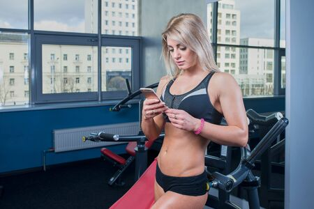 Fit girl poses with the cell phone in the gym in the black shorts and black top with the window in the background