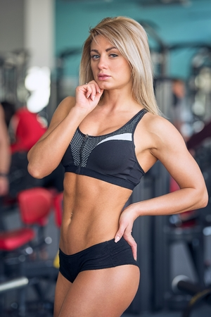 Fit blond girl in a black shorts and black top posing in the gym in the afternoon