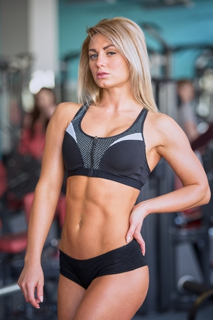 Fit beautiful blond girl with abs in a black shorts and black top posing in gym
