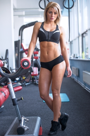 Fit beautiful strong blond girl with abs in a black shorts and black top posing in gym Stock Photo
