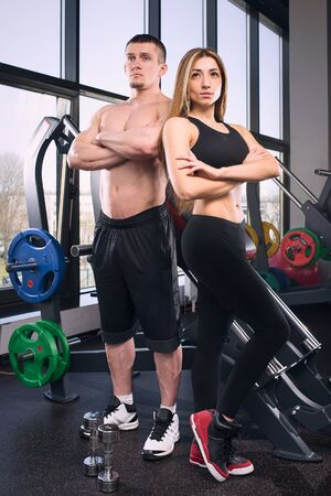 Muscular man and beauty girl posing near the window in gym